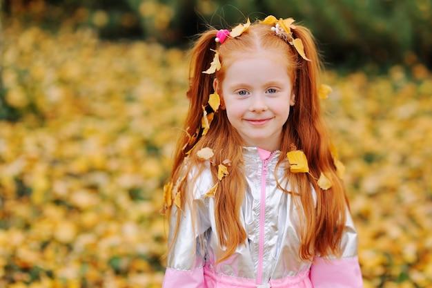 Bambina dai capelli con foglie cadute gialle sui capelli che sorride contro le foglie d'autunno nel parco.