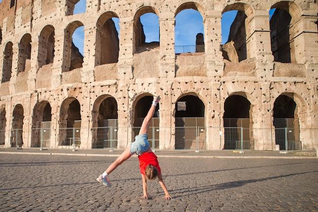Bambina davanti al colosseum a roma, italia
