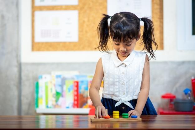 Bambina del bambino che gioca i giocattoli di legno