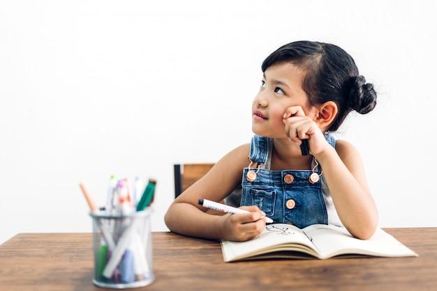 Bambina del bambino della scuola che impara e che scrive in taccuino con la matita che fa compito a casa