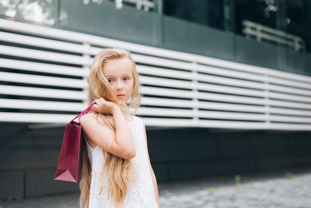 Bambina del colpo medio che posa con la borsa del regalo