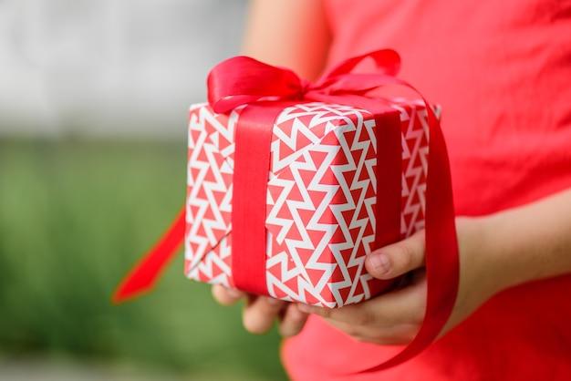 Bambina del primo piano che tiene un contenitore di regalo.