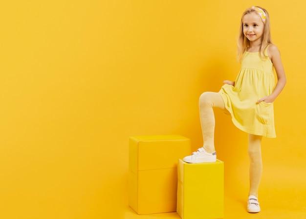 Bambina del ritratto in vestito giallo