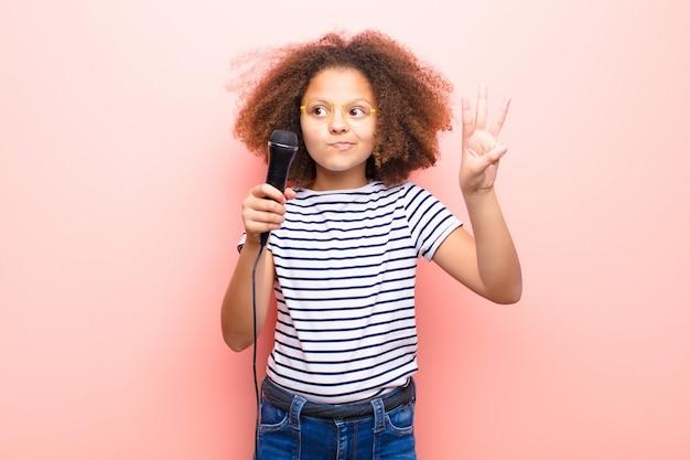 Bambina dell'afroamericano contro la parete piana con un microfono