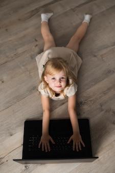 Bambina dell'angolo alto sul pavimento che esamina macchina fotografica