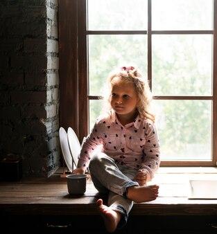 Bambina della foto a figura intera che osserva via