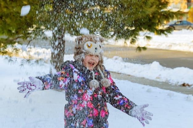 Bambina della neve di inverno che gioca con la neve