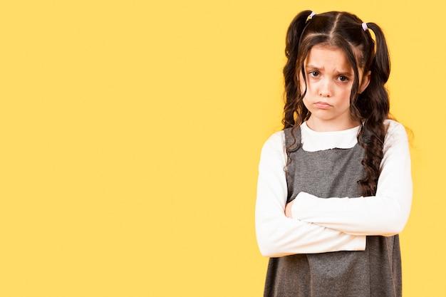 Bambina dello copia-spazio turbata su fondo giallo