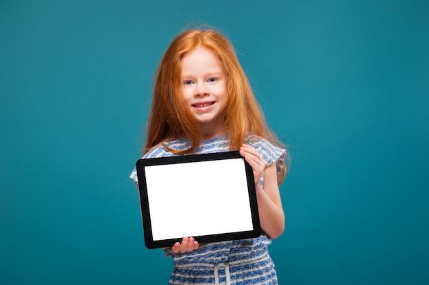 Bambina di bellezza in maglietta con la compressa della tenuta dei capelli lunghi