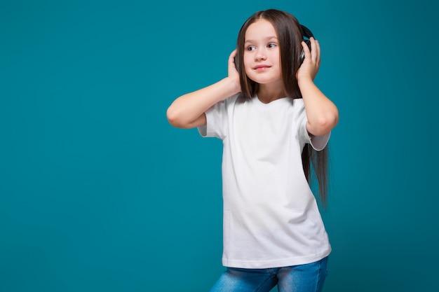 Bambina di bellezza in maglietta e cuffie con capelli lunghi
