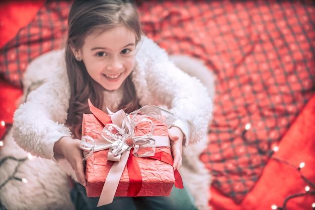 Bambina di concetto di festa e di natale con un regalo