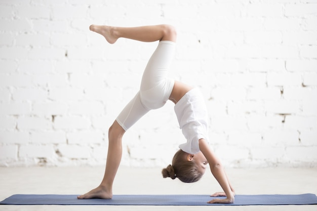 Bambina di ragazza in una gamba a forma di ruota, sfondo bianco studio