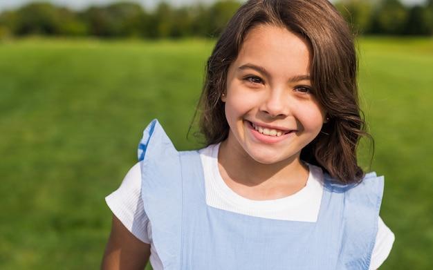 Bambina di smiley di vista frontale che esamina la macchina fotografica