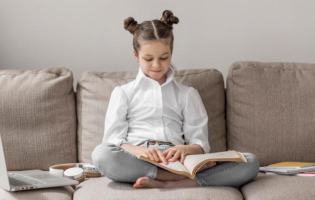 Bambina di vista frontale che impara sul sofà