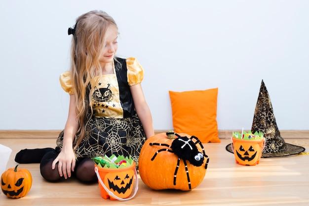 Bambina di vista frontale che si siede sul pavimento su halloween