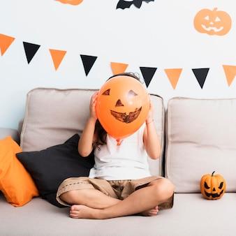 Bambina di vista frontale che tiene un pallone di halloween