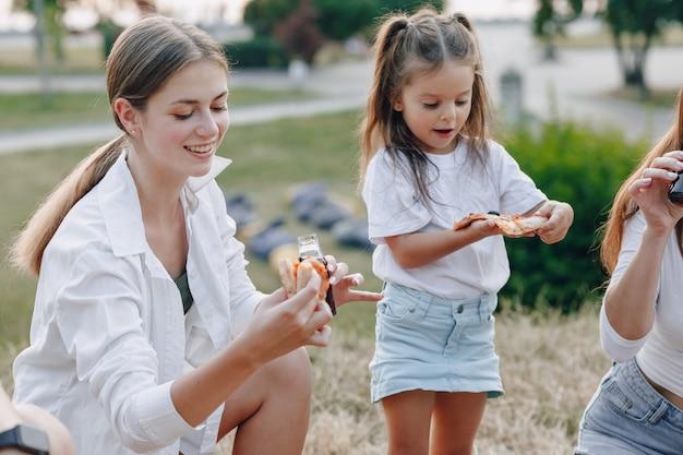 Bambina divertendosi al picnic con pizza
