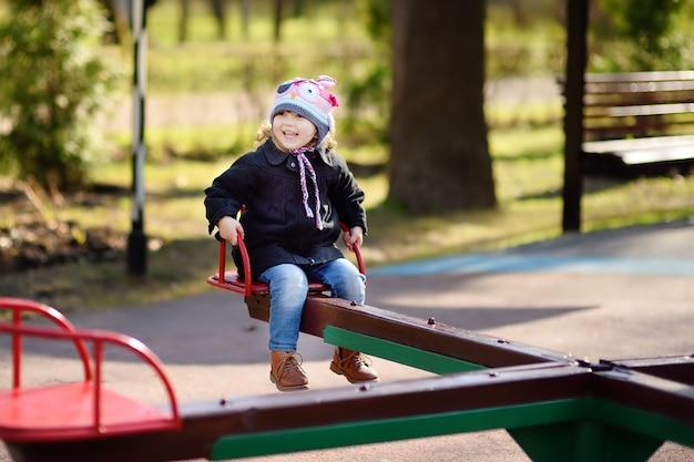 Bambina divertendosi con carosello sul parco giochi all'aperto
