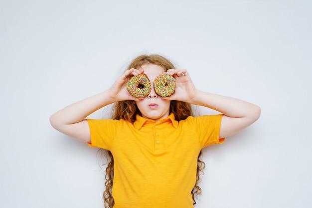 Bambina divertendosi con gli occhi di ciambelle.