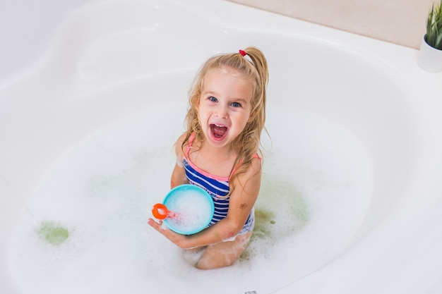 Bambina divertente che cattura il bagno di bolla