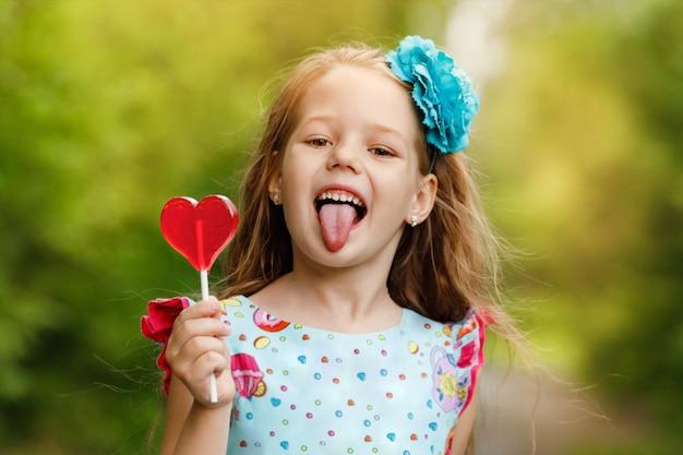 Bambina divertente con lecca-lecca a forma di cuore, mostrando la sua lingua.