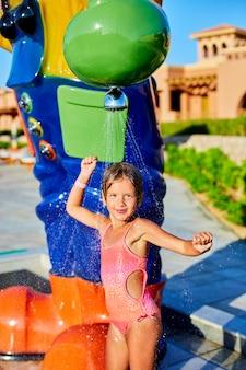 Bambina divertente in costume da bagno che si raffredda nella doccia fuori