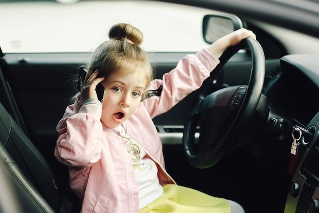 Bambina divertente sul sedile del conducente che finge di parlare al telefono