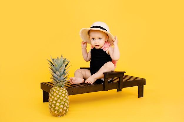 Bambina divertente vestita con un costume da bagno nero e rosa, grande cappello che si siede sulla sedia a sdraio in legno con ananas isolato su giallo