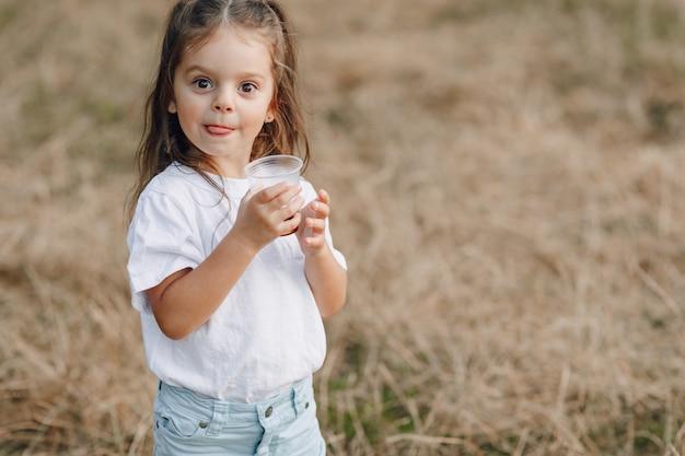 Bambina divertirsi al picnic, pizza, bevande, estate e prato