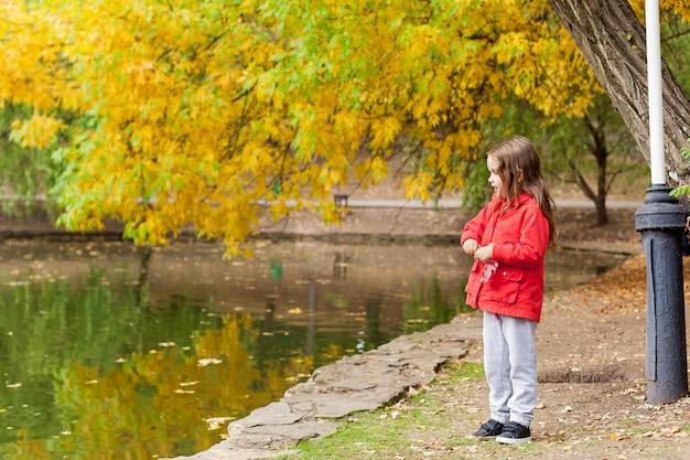 Bambina durante la passeggiata in un parco pubblico al freddo giorno di autunno soleggiato