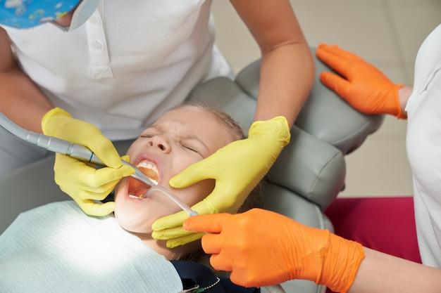 Bambina durante la procedura dolorosa in studio dentistico