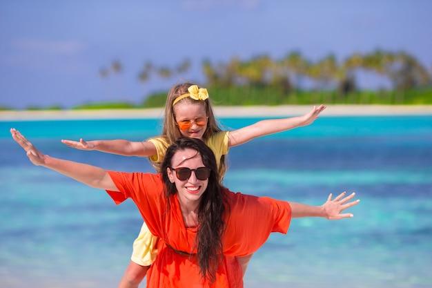 Bambina e giovane madre durante la vacanza della spiaggia