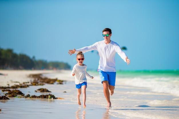 Bambina e giovane padre durante la vacanza tropicale della spiaggia
