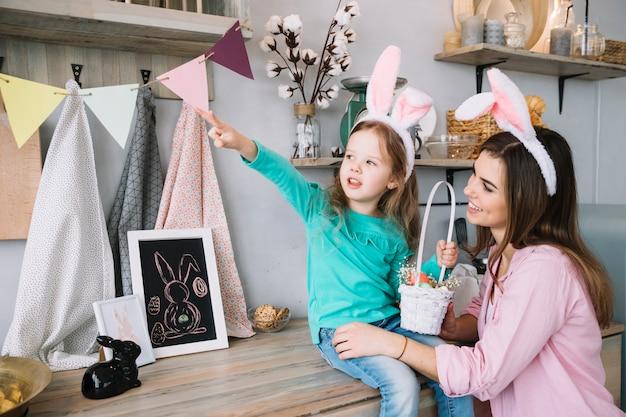 Bambina e madre nelle orecchie del coniglietto che si siedono con il canestro delle uova di pasqua