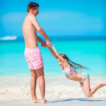 Bambina e papà felice divertendosi durante la vacanza della spiaggia