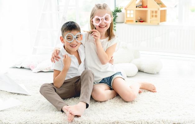 Bambina e ragazzo che indossa bicchieri di carta