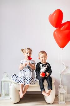 Bambina e ragazzo seduto su una sedia bianca vicino a palloncini a forma di cuore. ragazza che lecca una lecca-lecca rossa. concetto di san valentino.
