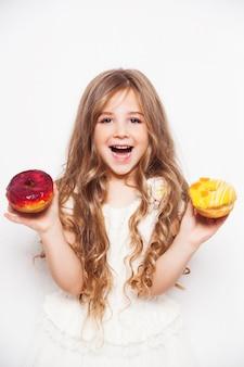 Bambina emozionante che posa con le ciambelle