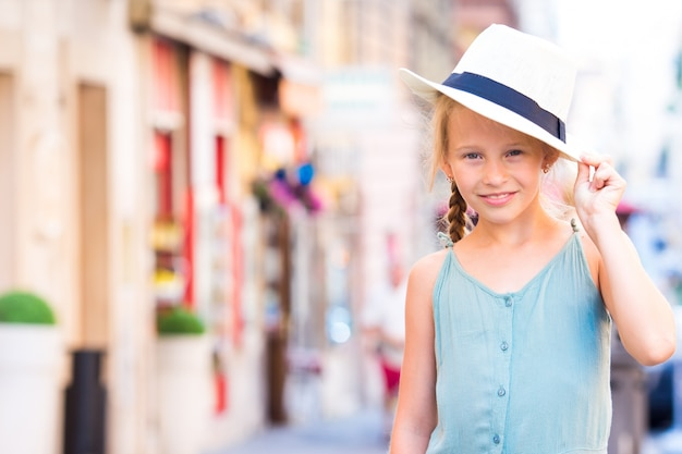 Bambina felice adorabile all'aperto in città europea.