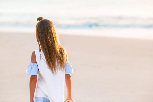 Bambina felice adorabile che cammina sulla spiaggia bianca al tramonto.