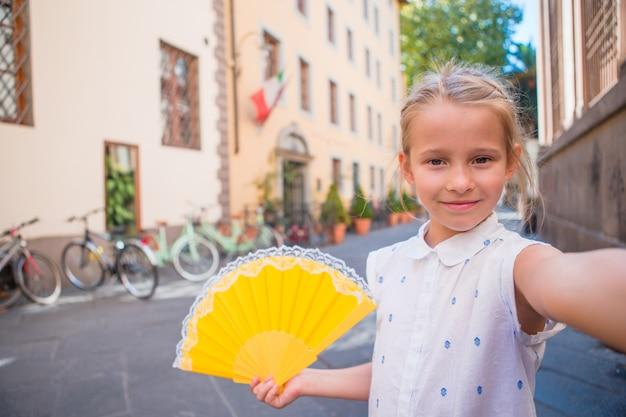 Bambina felice adorabile che prende selfie all'aperto in città europea. il ritratto del bambino caucasico gode delle vacanze estive nella vecchia città