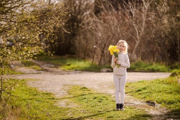 Bambina felice bionda sveglia con il paese giallo dei narcisi in primavera