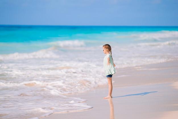 Bambina felice che cammina alla spiaggia durante la vacanza caraibica