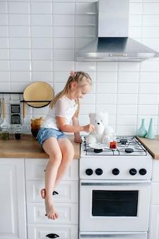 Bambina felice che gioca con gli orsacchiotti nella cucina bianca, giocando tea party