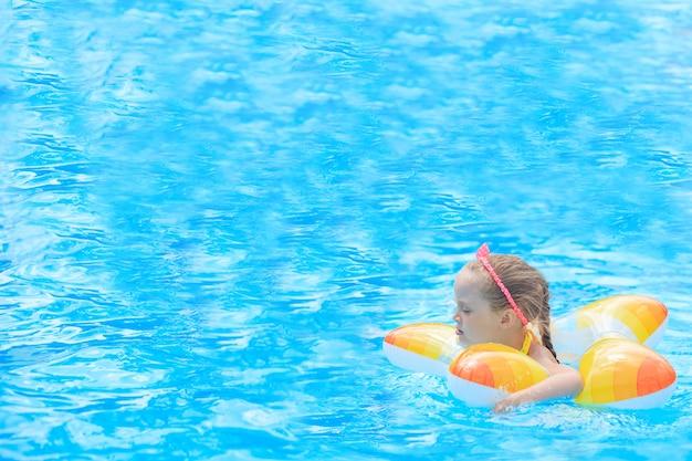 Bambina felice che gioca con l'anello gonfiabile variopinto nella piscina all'aperto il giorno di estate caldo. i bambini imparano a nuotare. giochi acquatici per bambini. i bambini giocano nella località tropicale. vacanza al mare in famiglia.