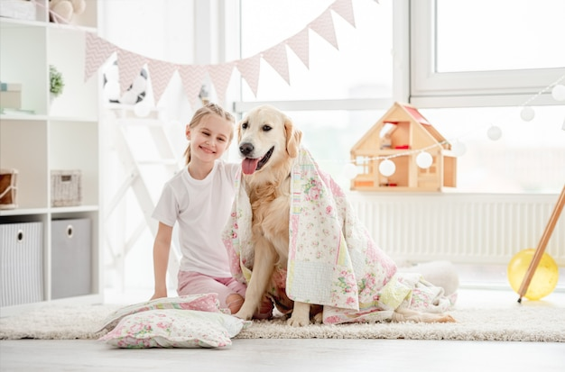 Bambina felice che gioca con un bellissimo cane