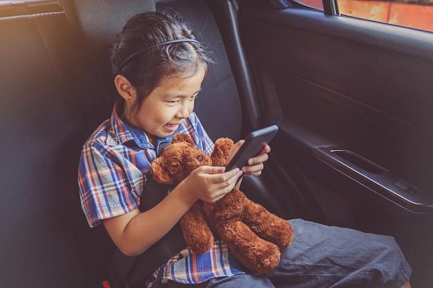 Bambina felice che indossa le cinture di sicurezza in auto