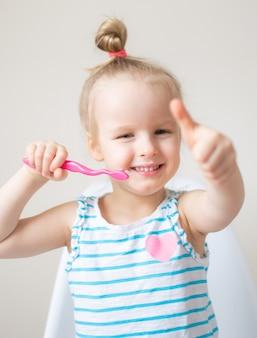 Bambina felice che pulisce i suoi denti, spazzolino da denti rosa, igiene dentale, stile di vita sano di concetto di notte di mattina