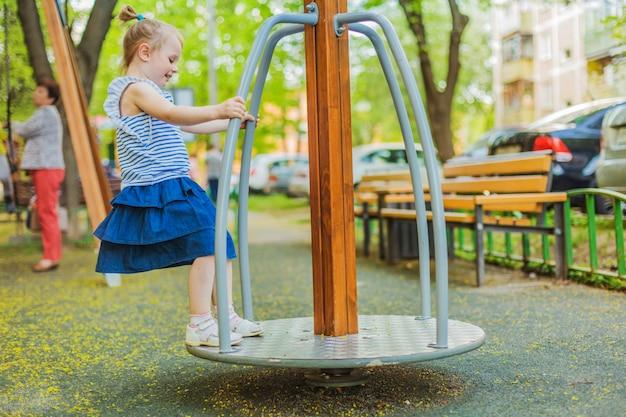 Bambina felice che si diverte in un parco giochi godendo di un giro giostra in una calda giornata estiva.