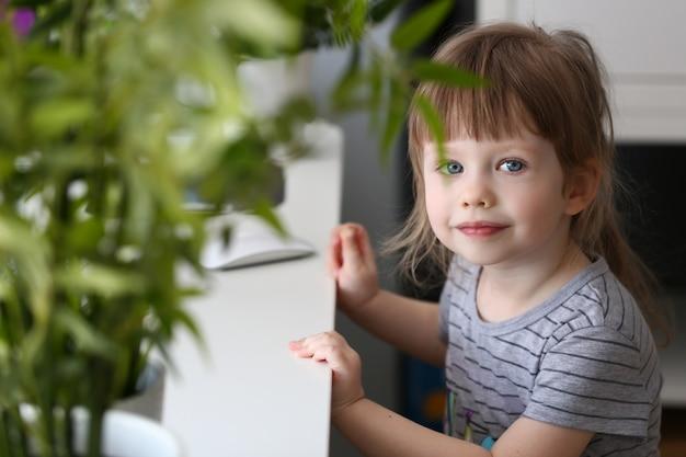 Bambina felice che si siede alla tavola che esamina